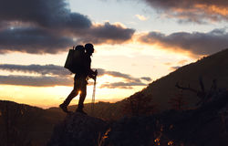 Young mountaineer standing with backpack on top of a mountain Royalty Free Stock Images