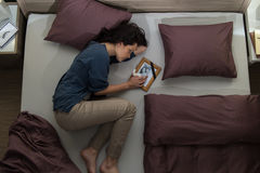 Young mourning woman lying in bed Stock Photos