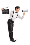 Young movie director shouting on a megaphone. Full length profile shot of a young movie director holding a clapperboard and shouting on a megaphone isolated on Royalty Free Stock Image