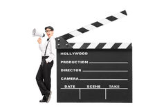 Young movie director speaking on a megaphone. And leaning on a giant clapperboard isolated on white background Royalty Free Stock Images