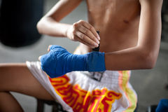 Young Muai Thai Boxer prepares for fight. A young thai boxer wraps his fist and hands in preparation for his fight in a slum camp in Bangkok, Thailand Stock Images