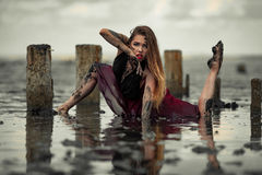 Young muddy woman in red dress is dancing in water on mud estuary. stock image