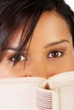 Young mulato woman hiding herself behind a book Royalty Free Stock Image