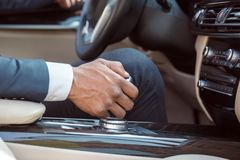 Young businessman driver sitting inside car holding gear shifter close-up royalty free stock images