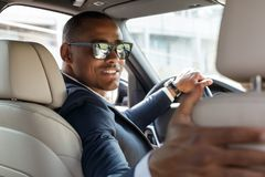 Young businessman driver in sunglasses sitting inside car driving holding steering wheel with one hand and seat with stock photos