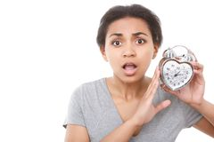 Young mulatto girl posing with alarm clock Royalty Free Stock Photography