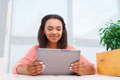 Young mulatto girl using tablet Royalty Free Stock Images