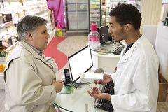 Young Mulatto male pharmacist speaking with a customer Stock Photo