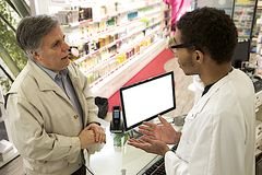 Young Mulatto male pharmacist speaking with a customer. Young mulatto male pharmacist speaking  at customer at pharmacy Royalty Free Stock Photos