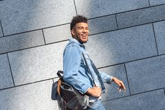 Freestyle. Mulatto guy carrying backpack walking isolated on wall laughing cheerful side view stock images