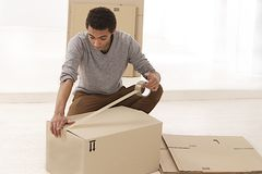 Young Mulatto man closing a moving box Royalty Free Stock Photos