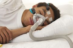 Young mulatto man with CRAP machine. Young mulatto man  sleeping with apnea and CPAP machine Stock Images