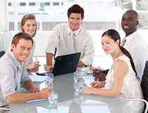 Young Multi Cultural Business Team at work. Young Multi Cultural Business Team smiling and working at desk Stock Photos