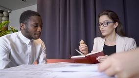 Young Multi ethnic African American experts discuss blueprint at informal meeting in restaurant. They communicate actively, look at drawings and point to stock footage