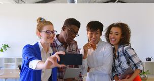 Young multi-ethnic business colleagues taking selfie with mobile phone in modern office 4k. Front view of young multi-ethnic business colleagues taking selfie stock video footage