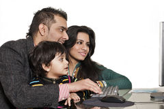 Young multi ethnic couple enjoying with their son. Happy multi ethnic family of three enjoying together Royalty Free Stock Image