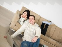 Young multi ethnic couple having wonderful time. Young couple having wonderful time in their luxury home and surfing internet Stock Photo