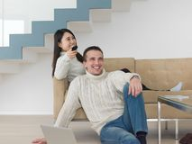 Multi ethnic couple on the sofa watching television Stock Image
