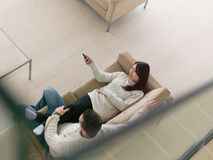 Multi ethnic couple on the sofa watching television Stock Photo
