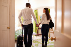 Young multi ethnic couple walk in to a hotel room, back view stock image