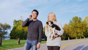 Young multi-ethnic couple walking in the park. Asian man talking on the phone, near the Caucasian woman walking with a stock footage
