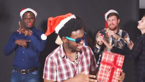 Young Multi-ethnic friends dancing at Christmas party in studio. stock video