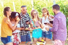 Young multi-ethnic friends having fun outdoor drinking red wine at open air bar-b-que party in countryside restaurant with