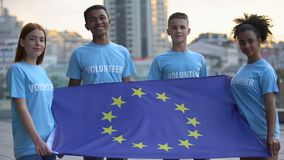 Young multi-racial volunteers holding European Union flag, international unity stock video