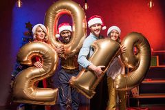 Young multicultural businesspeople in santa hats holding 2019 balloons at new year. Corporate party stock image