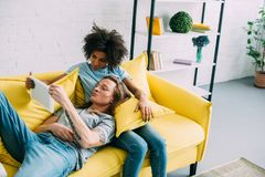 Young multicultural couple on couch looking at digital. Tablet screen royalty free stock photography