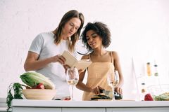 Young multicultural couple looking at recipe in book. At kitchen stock photo
