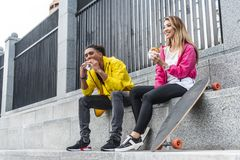 Young multicultural couple of skateboarders eating burgers. At city street stock photos