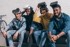 Young multicultural friends with lifted up virtual reality. Headsets stock photo