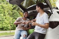 Multicultural friends standing near car. Young multicultural male friends sitting in open car back, drinking coffee with brofist gesture royalty free stock photo