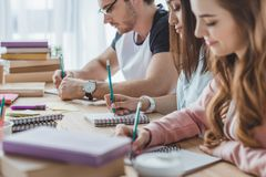 Young multicultural students writing. In copybooks stock photo
