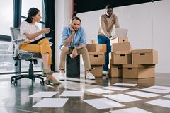Young multiethnic business people looking at papers on floor in new. Office stock photo