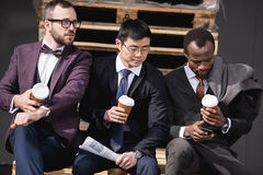 Young multiethnic businessmen in formalwear sitting at coffee break outdoors. Business team meeting Royalty Free Stock Photography