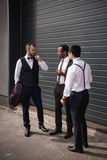 Young multiethnic businessmen in formalwear talking at break outdoors. Business team meeting Stock Photography