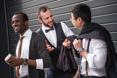 Young multiethnic businessmen in formalwear talking at coffee break outdoors. Business team meeting Stock Photo
