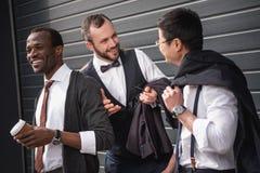 Young multiethnic businessmen in formalwear talking at coffee break outdoors stock photo