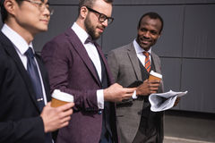 Young multiethnic businessmen in formalwear walking at coffee break outdoors. Business team meeting Royalty Free Stock Photos