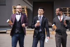 Young multiethnic businessmen in formalwear walking at coffee break outdoors. Business team meeting Stock Images