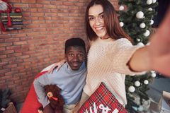 Young multiethnic couple meeting Christmas hugging home. New Year. Festive mood of a man and a woman Royalty Free Stock Image
