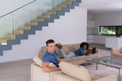 Young multiethnic couple relaxes in the living room Royalty Free Stock Photos
