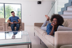 Young multiethnic couple relaxes in the living room Stock Image