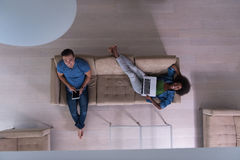 Young multiethnic couple relaxes in the living room top view Stock Photos