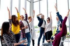 Young multiethnic diverse creative asian group huddle and high five hands together in office workshop with success or empower stock photo
