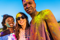 Young multiethnic friends with colorful paint on clothes having fun together at holi festival. Cheerful young multiethnic friends with colorful paint on clothes Stock Image