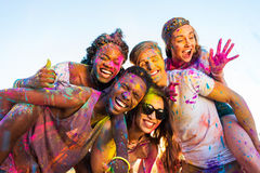 Young multiethnic friends with colorful paint on clothes having fun together at holi festival. Happy young multiethnic friends with colorful paint on clothes Royalty Free Stock Photo