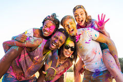 Young multiethnic friends with colorful paint on clothes having fun together at holi festival. Happy young multiethnic friends with colorful paint on clothes Royalty Free Stock Images